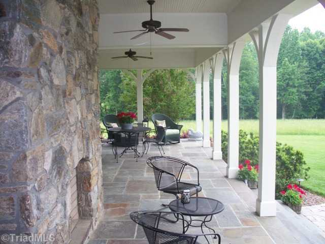 Loggia with custom stone fireplace and flagstone floors
