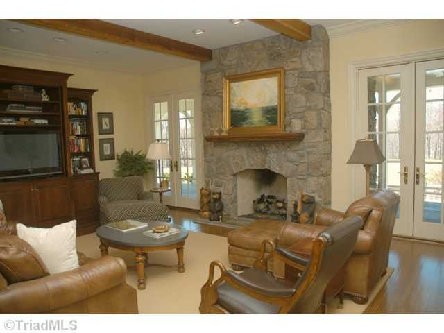 Great Room with wooden beams and a floor to ceiling stone fireplace
