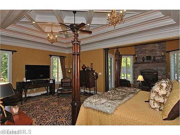Master Bedroom Suite with coffered ceiling and a stone fireplace