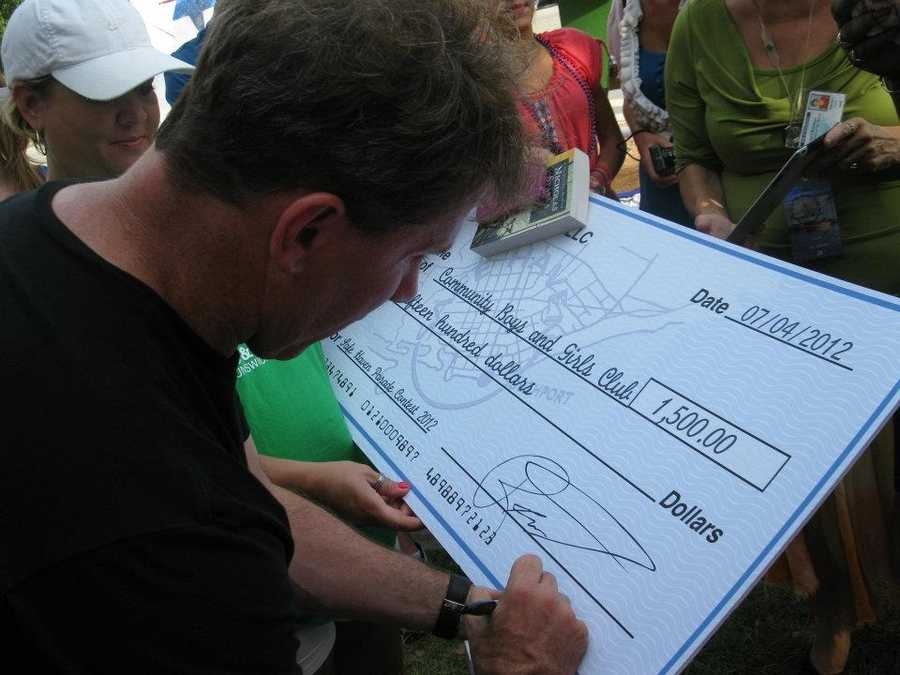 This is the author of Safe Haven, Nicholas Sparks. He writes a check for a boys and girls club that built the best float.