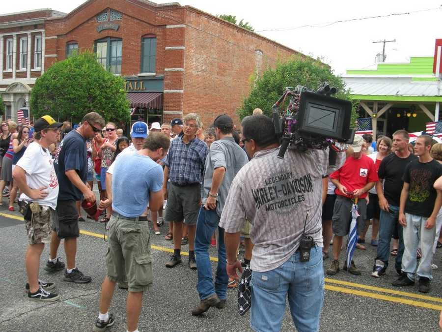 Members of the film crew talk in between sets. The man in the dark blue jeans and gray shirt reaching into his back pocket is one of the actors for the film. His name is David Lyons.
