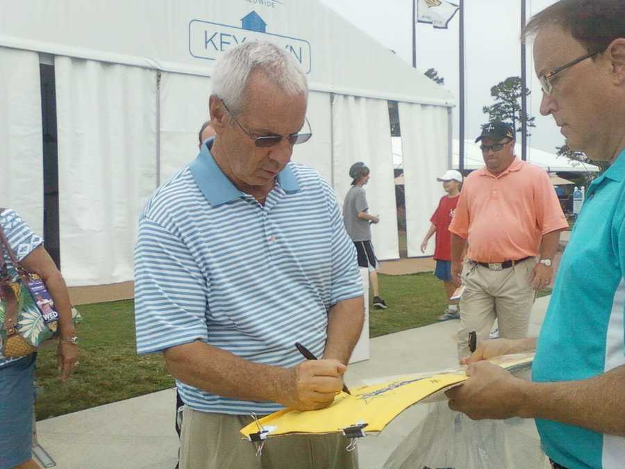 UNC basketball coach Roy Williams signs an autograph.