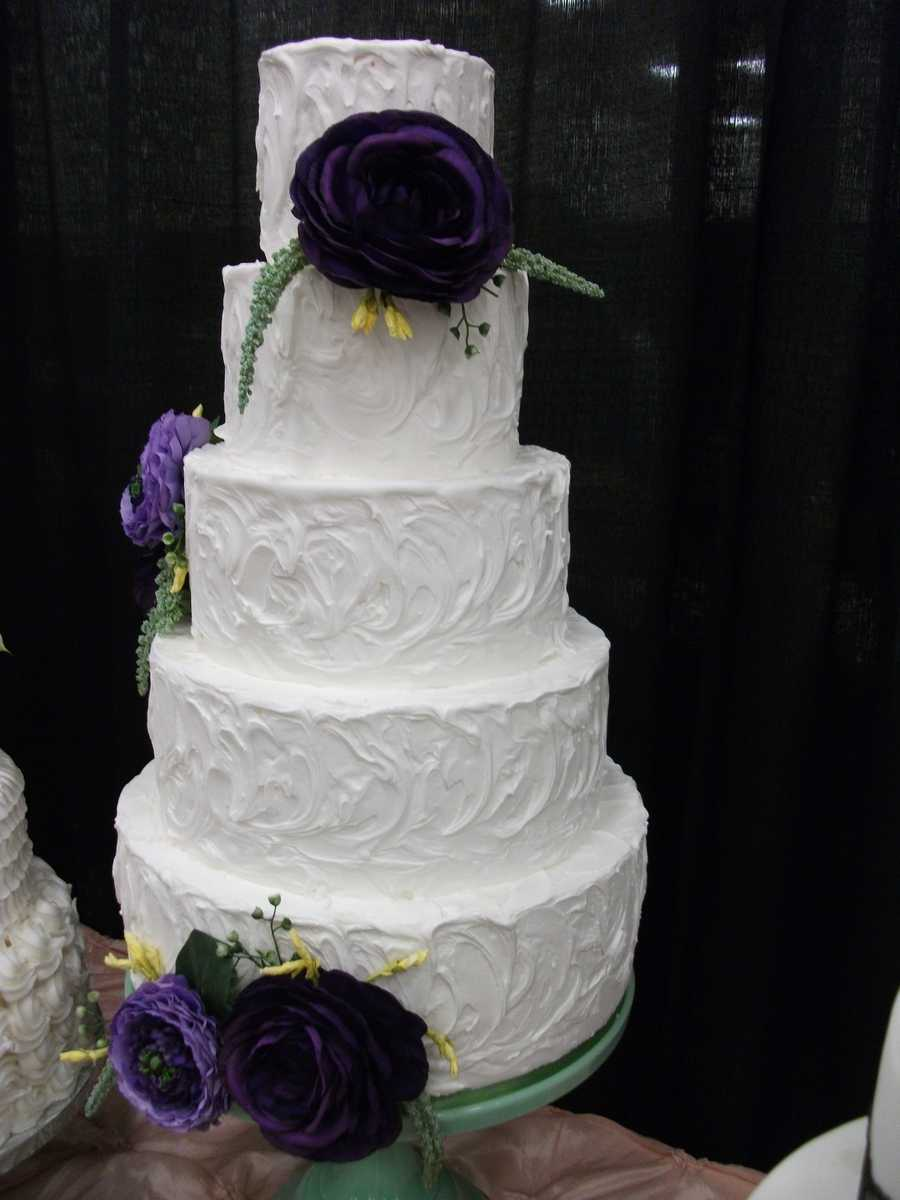 This traditional fancy swirl white cake could be decorated flowers in your wedding colors and still be a part of your theme...(Cake and All Things Yummy)