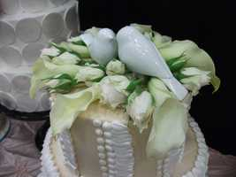 This cake topping is unique with real flowers and love doves...(Cake & All Things Yummy)