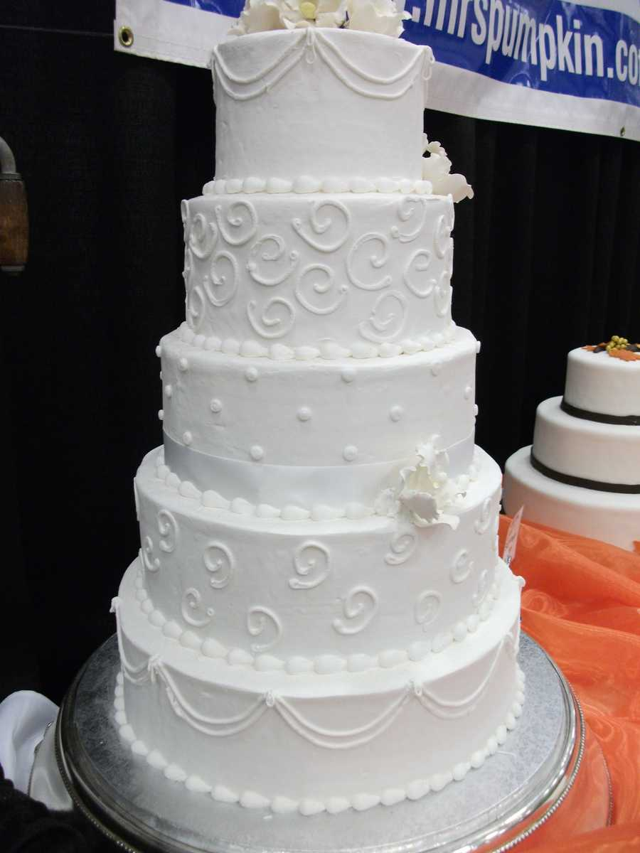 Traditional beautifully styled white wedding cake would make the Red Carpet Theme show through. (Mrs. Pumpkins)