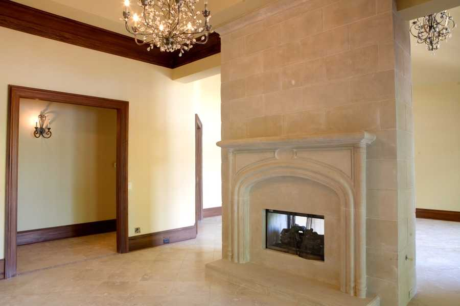 Formal Living Room with a limestone wall which features a double-sided fireplace
