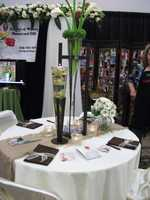 Beverly's Midway Flowers and Gifts had interesting reception pieces in their booth. The tablescapes with candles and tall vases with floating orchids then a twist with another taller flower decoration.