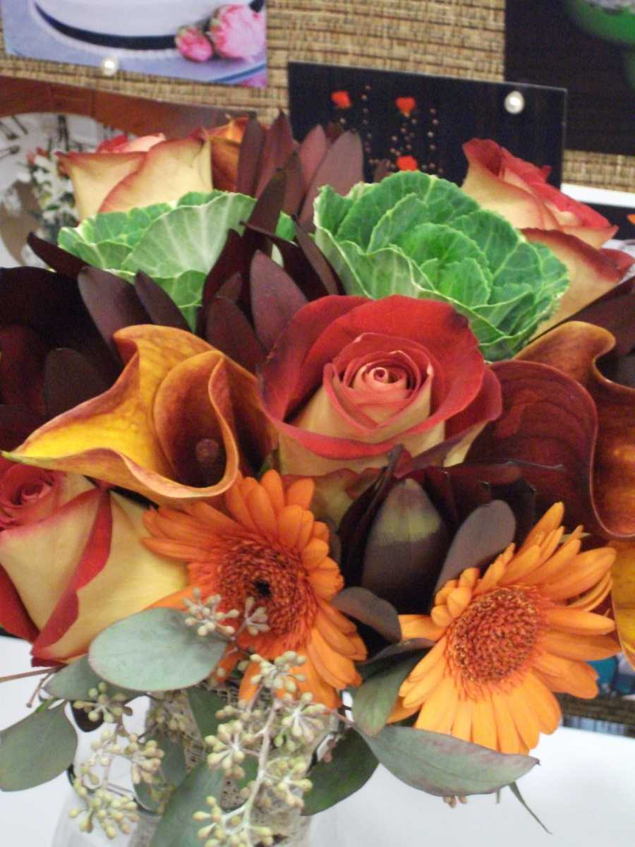 Beautiful fall colors with a little something different added. Don't be scared to add little touches of something unique. (Beverly's of Midway Flower's and Gifts)