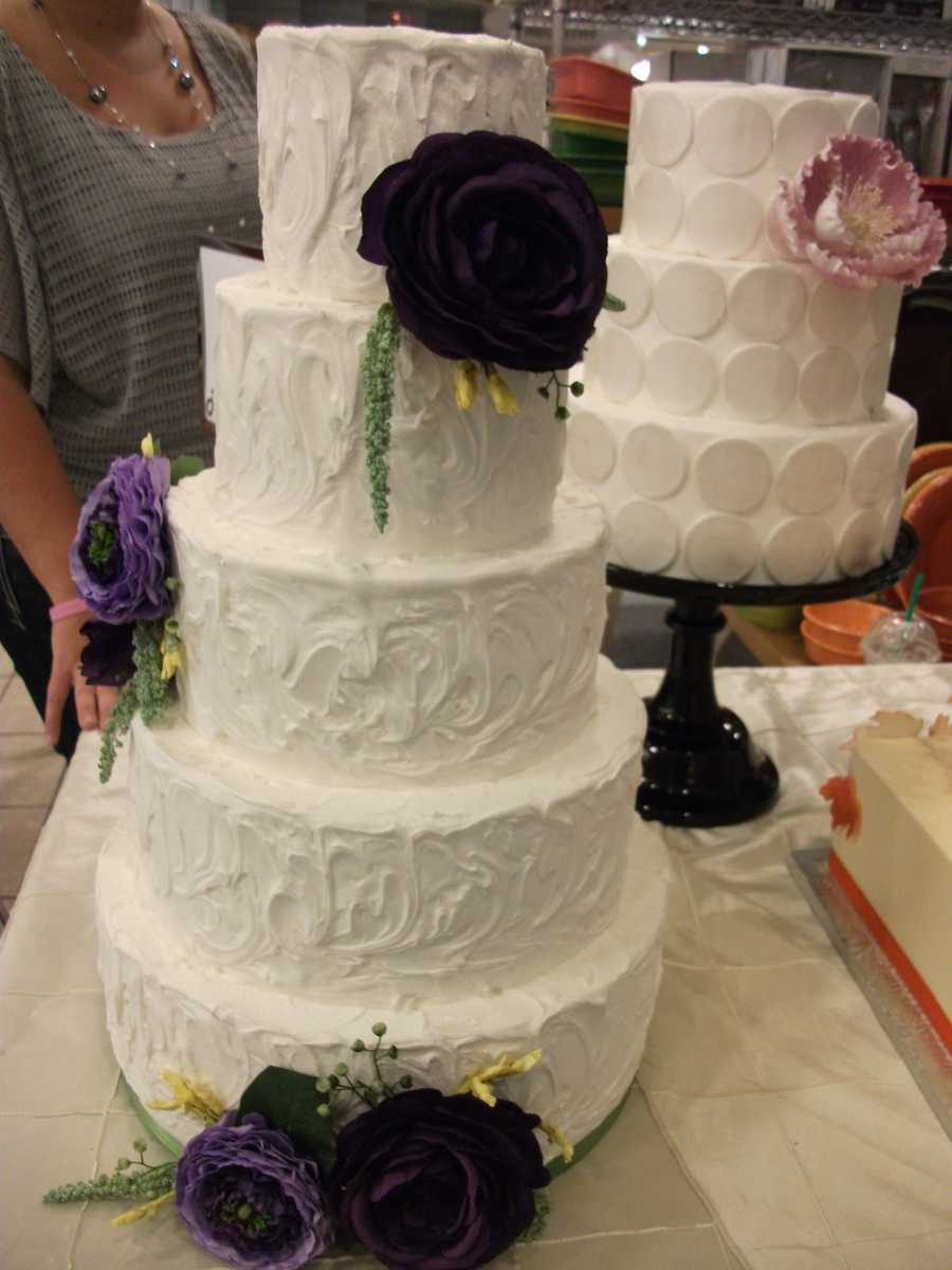 All these cakes are basic white with touches of colorful flowers and designs that can make any couples wedding reception pop. (Cake and All Things Yummy)