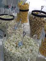 Several kinds of popcorn and candies can be served on a popcorn and candy bar at the reception. (The Popcorn Fanatic)