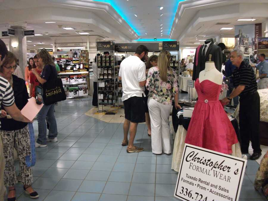 Groups of people check out the Christopher's Formalwear booth and others.