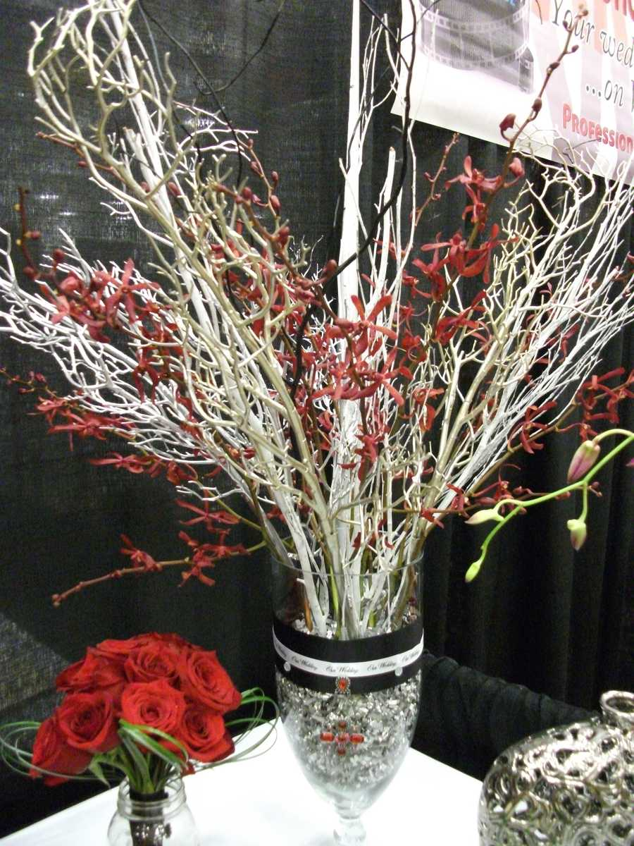 This arrangement shows the fall of the leaves in autumn but still some life with the beautiful red flowers intertwinedin the branches. (Dahlias Flowers)