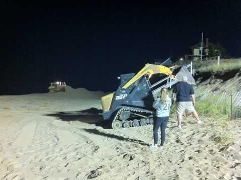 Piling up sand late Sunday night in Plum Island, Mass.
