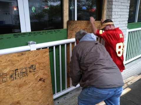 Residents in Ocean City, Md., board up windows Sunday as Hurricane Sandy nears.