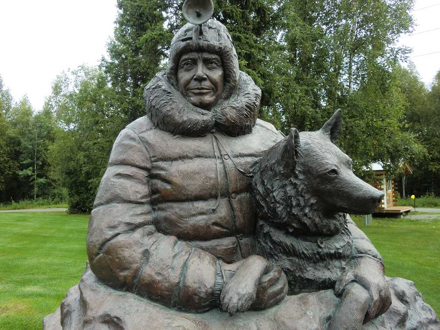 """Joe Reddington, Senior was considered the """"Father of the Iditarod Trail Sled Dog Race"""" and here is a statue in honor of him in Wasilla, Alaska with a sled dog."""