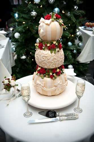 The wedding cake looks magical and could be used for a fairy tale wedding but the theme is Christmas with the beautiful roses and bows.
