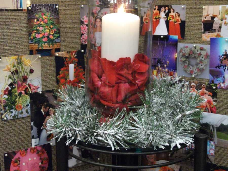 Pine needles sprayed to look like snow or branches with the red roses and candle look great for a Christmas or Winter themed wedding. (Beverly's of Midway Flowers & Gifts)