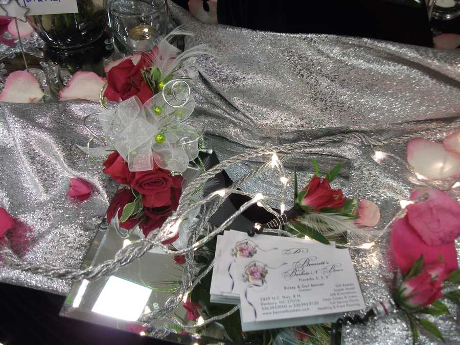 This mixture of the silver along with red, white/pink tipped flowers and pedals with mirrors and candles go good for a table at the reception. Maybe even the bride and groom's table. (Bennett's Baskets N Bows)