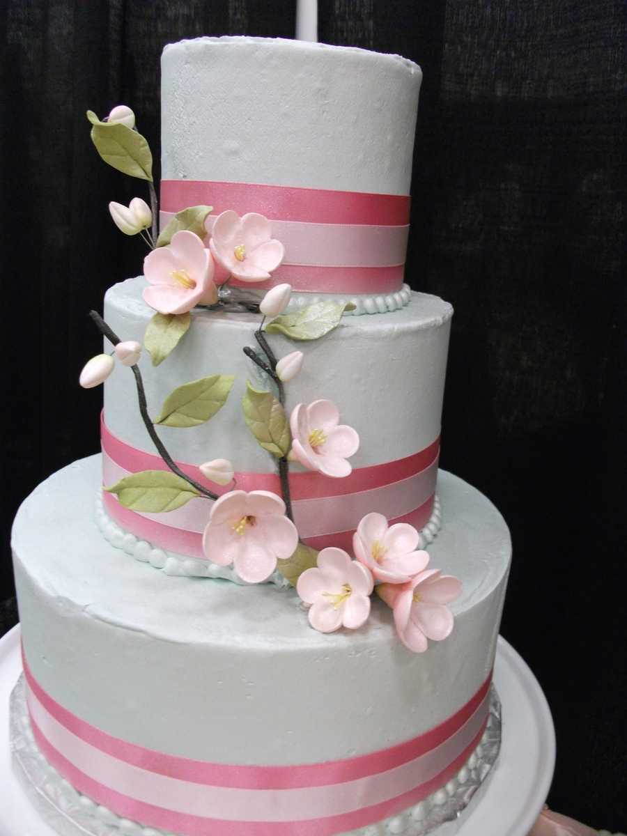 This pink ribbon and white cake decorated with beautiful edible pink flowers is incredible for the wedding cake. (Cake & All Things Yummy)