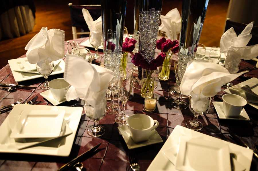 The small vases with single cut red flowers pop with the white table setting and the chocolate tablecloth to make this reception table all about the love theme.
