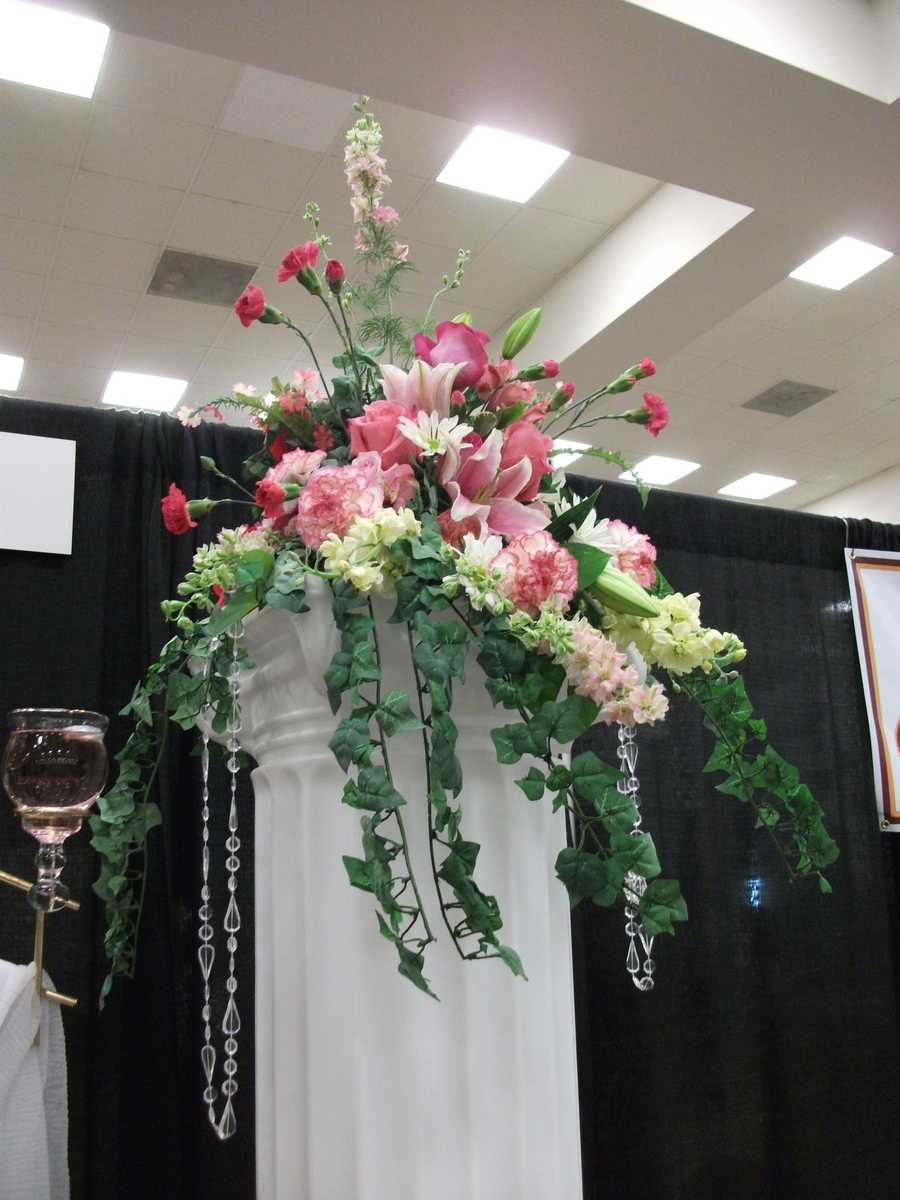 Maybe you want one or two columns with an arrangement adorning it at the end of the row where the wedding will take place or as decoration in a church. (Bennett's Baskets N Bows)