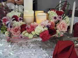 Make your own table setting and give her a nice Valentine's Day dinner. Then pop the question. These same flowers, candles and even rose table cloths could be used at your reception. (E'MAGINE WEDDINGS AND EVENTS)