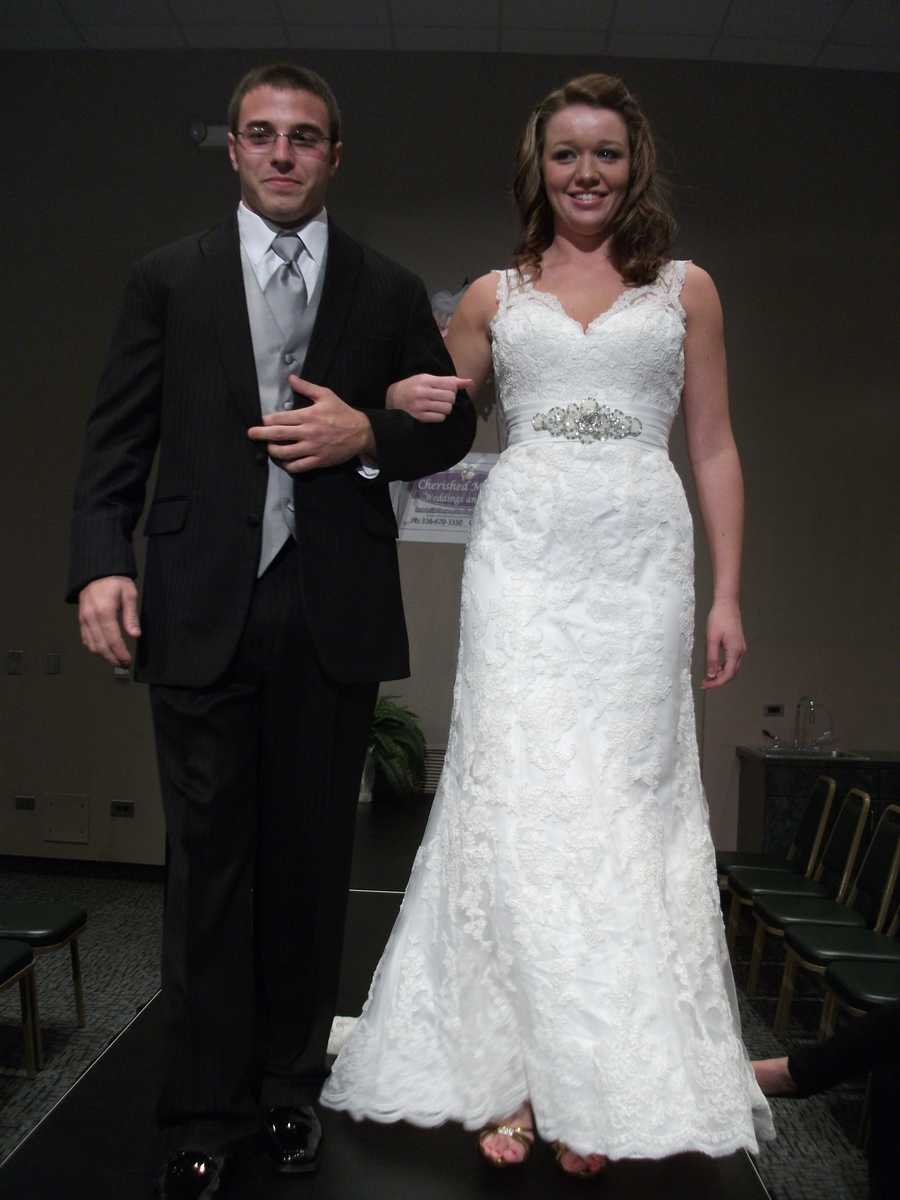 The lace on this dress is beautiful and would make a great Country/Western Themed wedding. The silver design on the dress goes great with the grooms grey vest and tie.