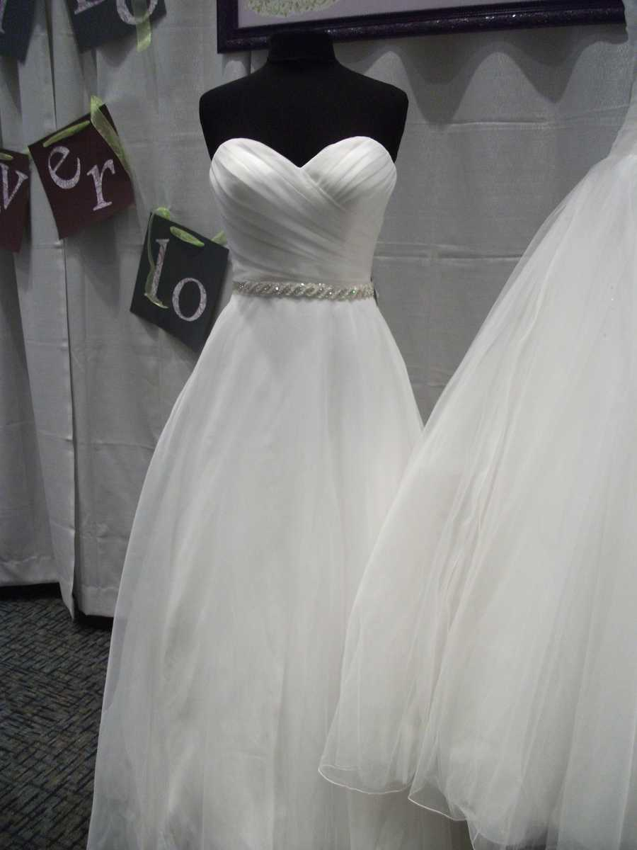 This beautiful wedding dress has a silver sash around the waistline to make it very small then a nice flowing material for the train. Bridal Traditions Wedding and Prom Attire