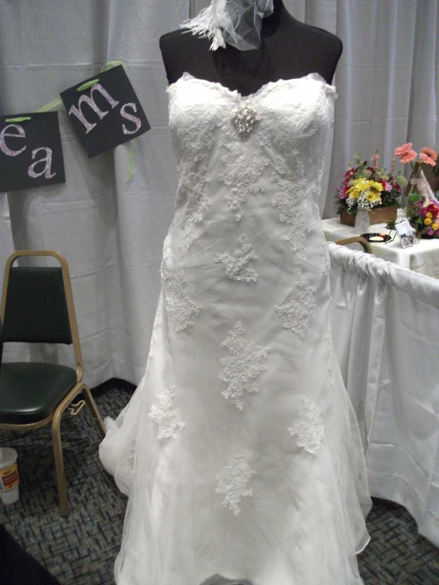 "Bridal Traditions Wedding and Prom Attire had this bridal gown in it's booth which had a lot of character with it's lace. They would make a great ""Hollywood/Red Carpet Themed Wedding Dress."" The broach and feathers make it even more glamorous."