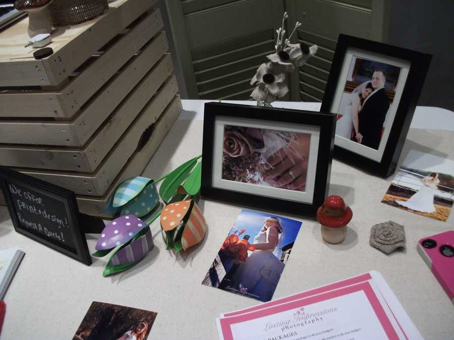 Lasting Impressions Photography table at their booth had nice decor and photos from several weddings.