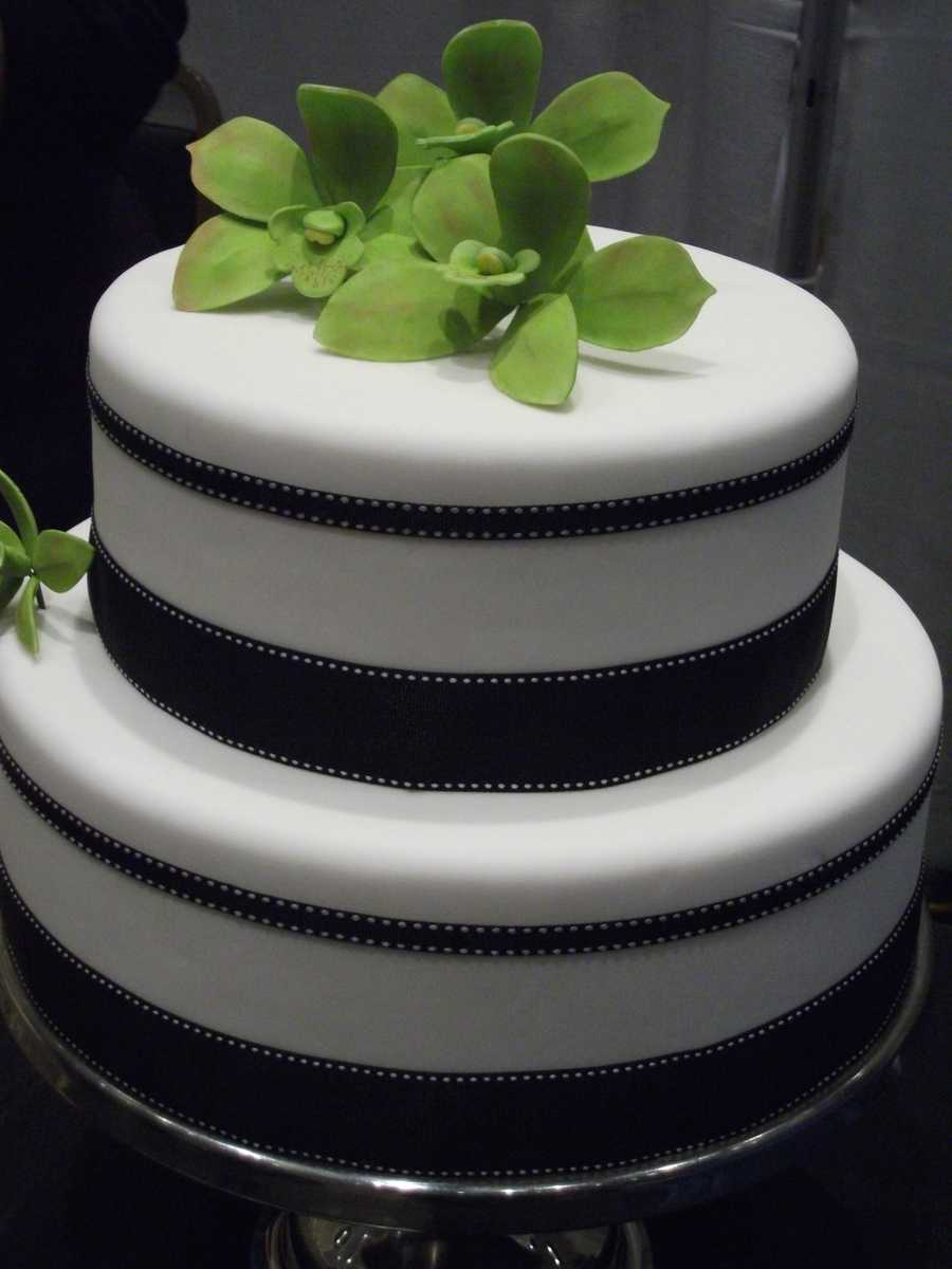Purple Moon Cakes and Confections has this very elegant looking, but sleek cake. Maybe this black and green cake with gum paste orchids have your wedding theme colors?