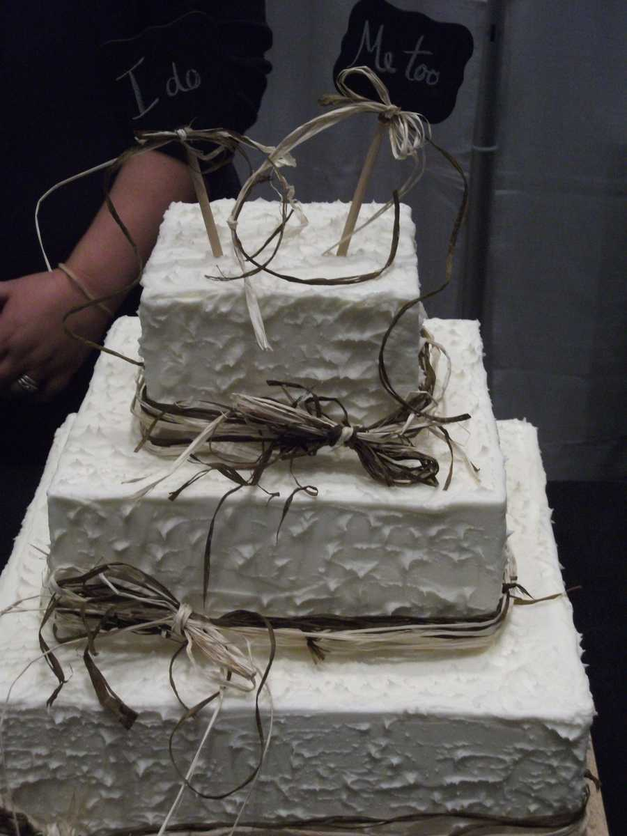 """This """"Rustic"""" butter cream cake with raffia (straw) and neat chalk signs for the topper makes a great nature or Country/Western themed wedding cake. (Purple Moon Cakes and Confections)"""