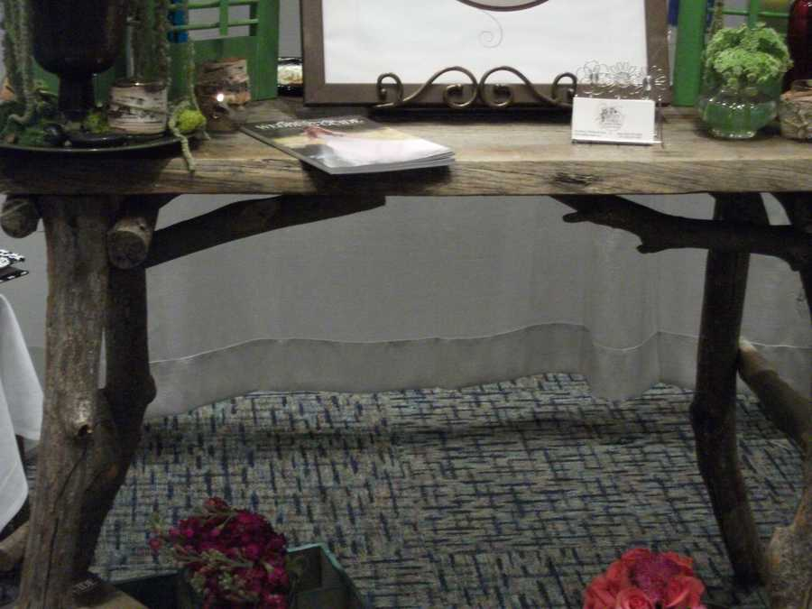 This table would make a great area at the reception for photos, signing, seating name cards or even a dessert table for a nature/Eco-friendly or country/western themed wedding. (Desi's Floral & Design Studio)