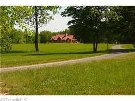 This Mocksville custom cedar home is situated on 140 acres and priced at $1,450,000. The property includes a caretaker's home, barn and five stocked ponds.