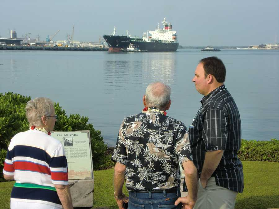 Austin and Ben, a retired Greensboro firefighter and fellow traveler looking at the open Hawaiian Bay while chatting.
