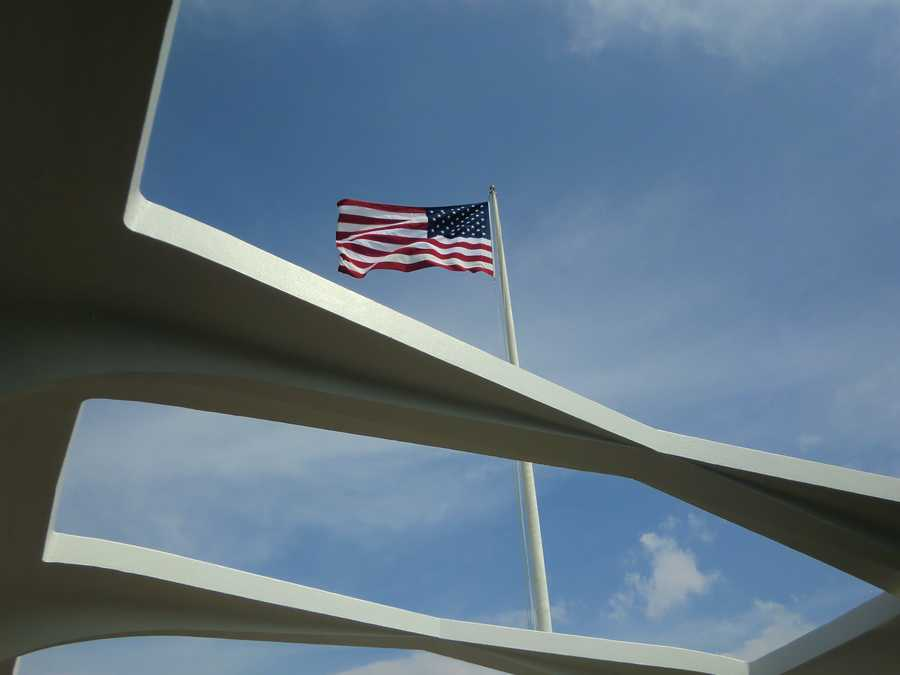 """An American Flag is flying over the memorial. Although the U.S.S. Arizona was stricken from the official register of U.S. naval vessels after the attack she was symbolically """"re-commissioned"""" when a flagpole was erected on the ship."""
