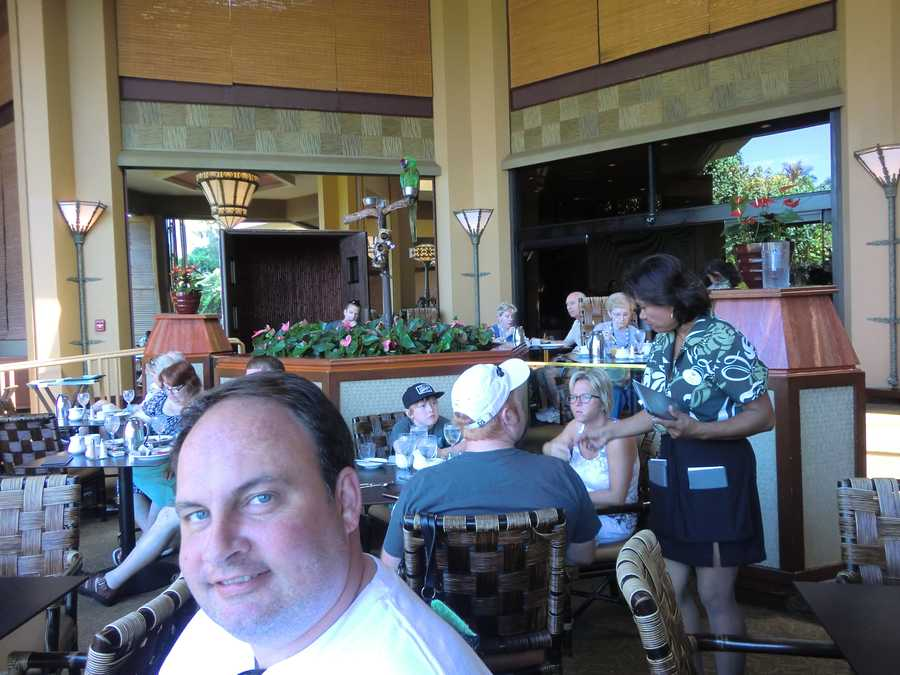 Austin enjoys breakfast while the hotel parrot in Maui entertains the guests.