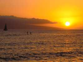 See surfboard paddles and sailboats while the sun sets from Lahaina's famous Bubba Gump Restaurant.