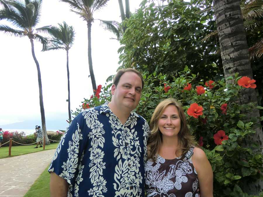 Austin and Angela pose for a photo beside some beautiful flowers with palm trees swaying in the breeze.