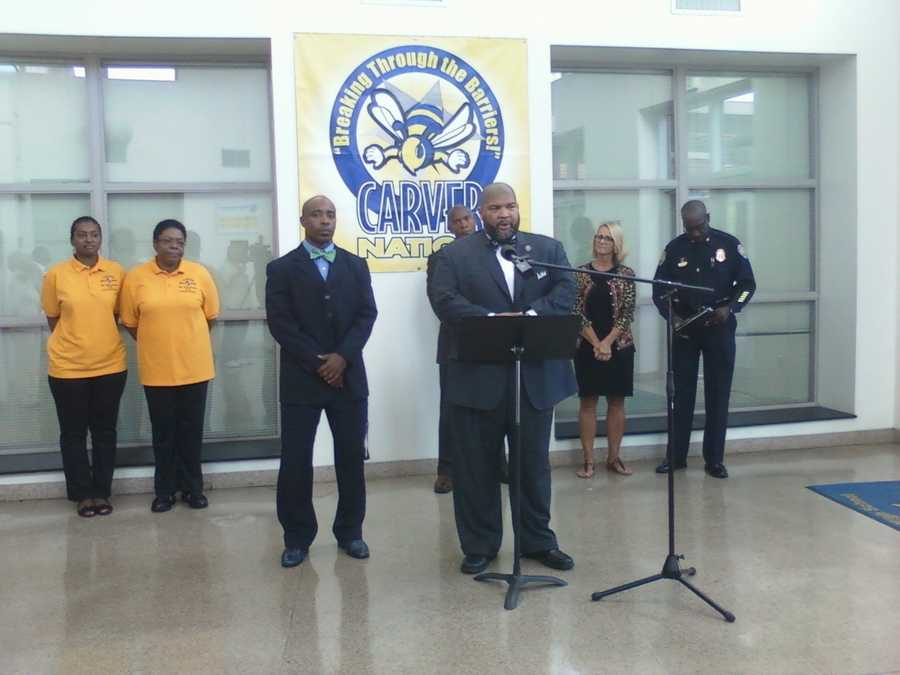 Carver High School Principal Ron Travis talks to reporters Monday. Behind him are Superintendent Beverly Emory and police Chief Barry Rountree.