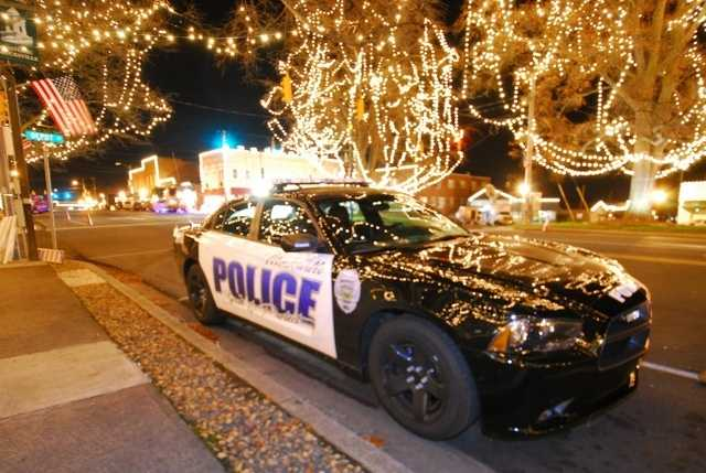 A Mocksville police car is parked under several trees covered in Christmas lights.