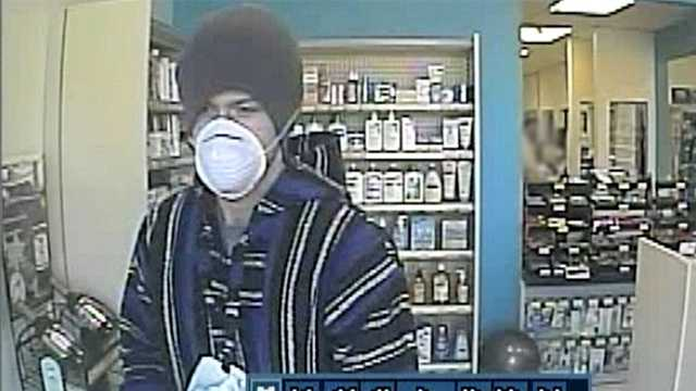 Surveillance image of Piedmont Drug robbery suspect (background partially blurred)