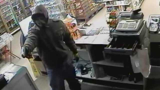 Surveillance image of convenience store robbery at gunpoint