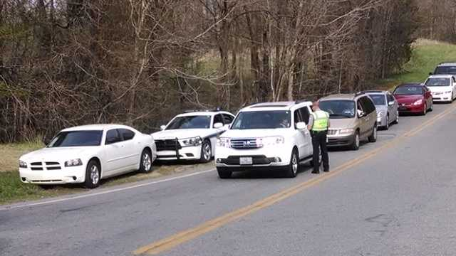 Law enforcement stopping cars near body discovery site