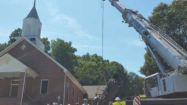 Crews work to upright a piece of equipment involved in a deadly accident next to a Wilkes County church Tuesday.