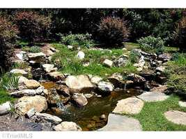 Waterfall feature spills into a small pond