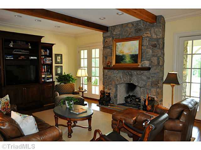 Family Room with a stone fireplace and beamed ceiling