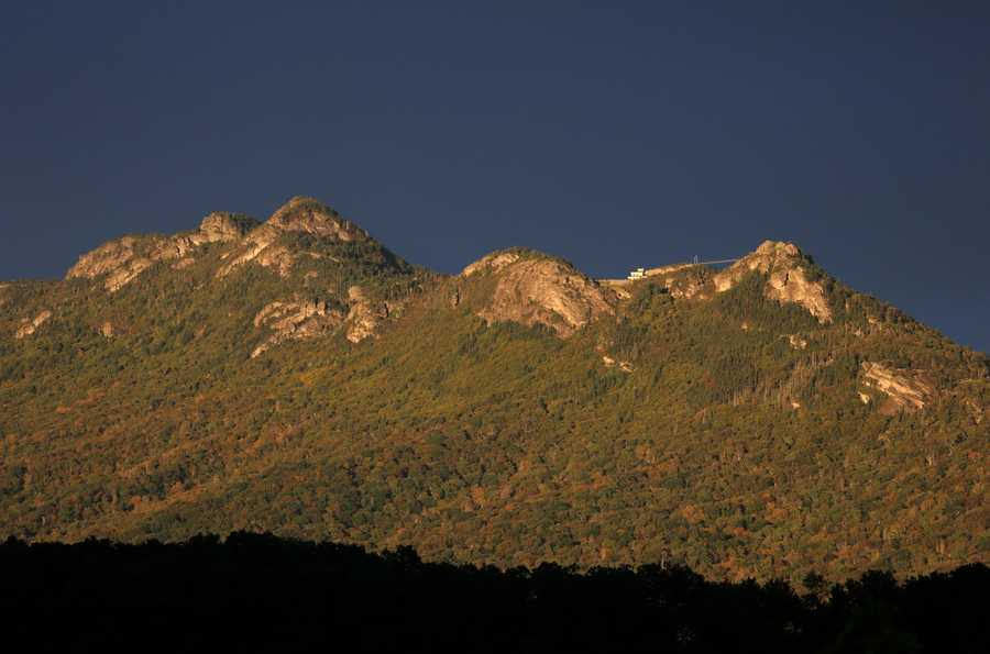 Sept. 27:Afternoon sun hitting the western slopes of Grandfather Mountain inLinville shows fall color trickling into western North Carolina. (Photo by Jim Morton)