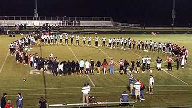 Students from Rolesville and Southeast Raleigh high school pray after a player collapses before a high school football game Friday.