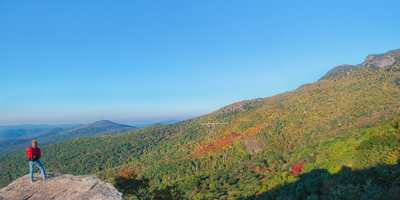 Oct. 5: A hiker gazes at the beauty from Rough Ridge, looking south toward the Linn Cove Viaduct and the peaks of Grandfather Mountain. (Photo by Skip Sickler)